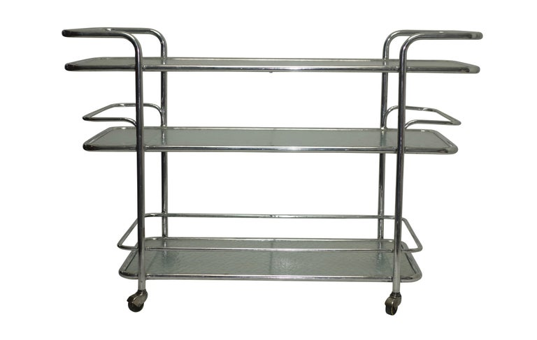 A three-tier polished aluminum serving cart or drinks cart with textured glass shelves on rolling wheels. American, circa 1950.