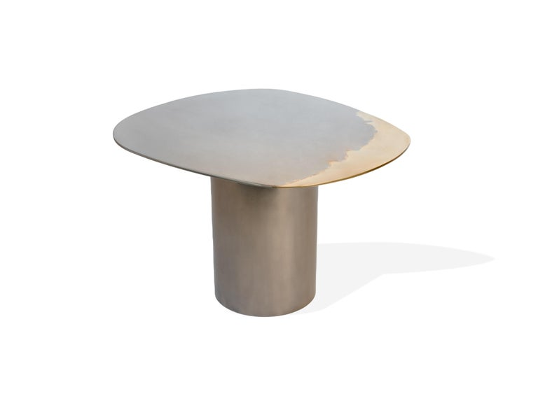 A side table as part of the Transition collection, featuring a unique, artistic mirror polished tabletop, crafted from brass and stainless steel on a tubular base. 
