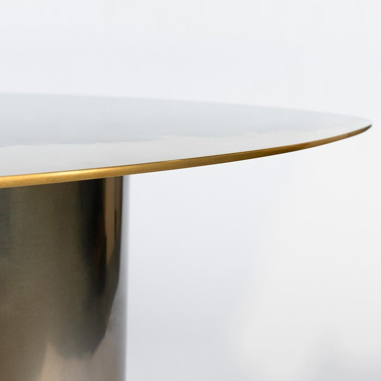 """A side table as part of the Transition collection, featuring a unique, artistic mirror polished tabletop, crafted from brass and stainless steel on a tubular base. Measures: H 22"""".  Studio Warm has developed a distinctive, high-end, artistic"""