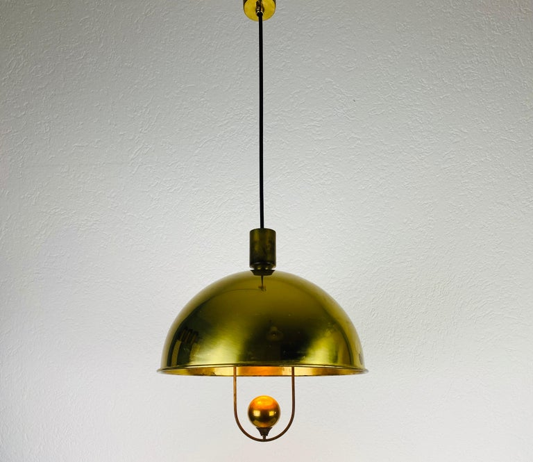 Extraordinarypolished brass pendant lamp designed by Florian Schulz and made in Germany in the 1970s. It is fascinating with its Exclusive Design. The height of the lighting is adjustable.  Measurements of shade: Max height 84 cm Height 36