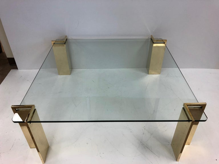 Polished bronze and glass coffee table. Glass is approximately one inch thick. Four individual bronze bases which weighs approximately 22 pounds each.