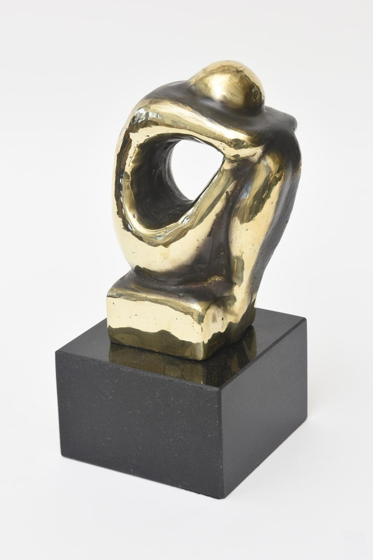 This arresting and handsome seated figurative abstract brass and granite sculpture is handsome and powerful. It is Spanish and is a limited edition number. Part of the brass has been polished and the remainder is a beautiful two-tone patina. The