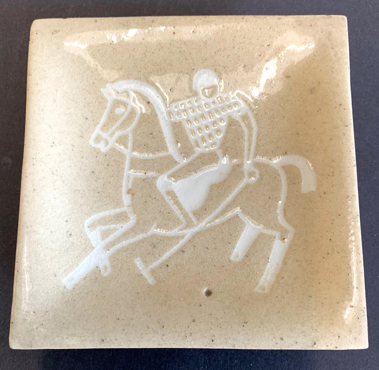 Beautifully glazed in shades of white and sand, this rare footed dish depicts a polo player reaching out to strike the ball. The primary glaze has a beautiful mottled appearance, and the artist -- Waylande Gregory -- very cleverly represented the