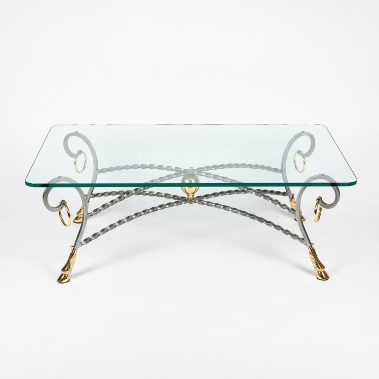 A polo themed steel and brass hoof foot coffee table with glass top.   Wrought twisted steel base with brass ball, hoof feet and rings.