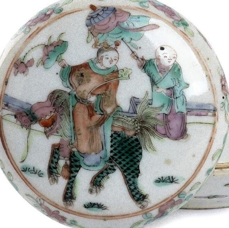 This polychrome porcelain box and cover is a superb decorative object, realized in China in the early 20th century.  The domed lid is decorated with a scene depicting a boy on a mythological animal, at his back there is another boy playing with a