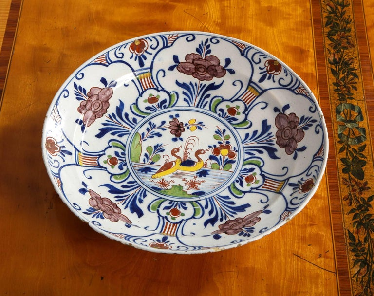 Fine 18th century Dutch delft charger/deep dish featuring two ducks in a pond with foliate decorated border, in manganese, yellow, blue and green glazes, having pottery mark