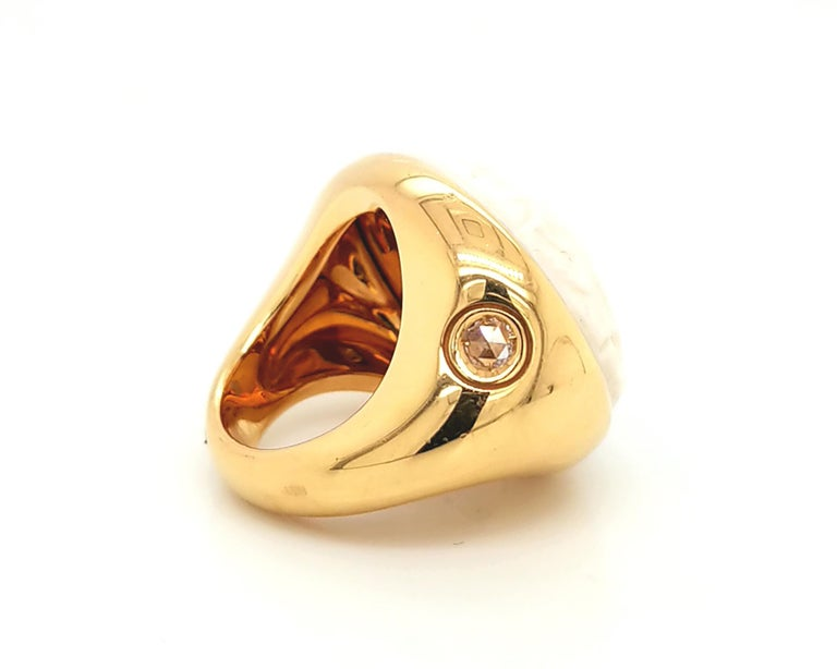 A beautiful cocktail ring created by an Italian jewelry company Pomellato. The ring is featuring a 15 carat carved agate stone and a 0.14 carat rose-cut diamond on the side. The metal is 18K yellow gold. Signed Pomellato. Size 6.