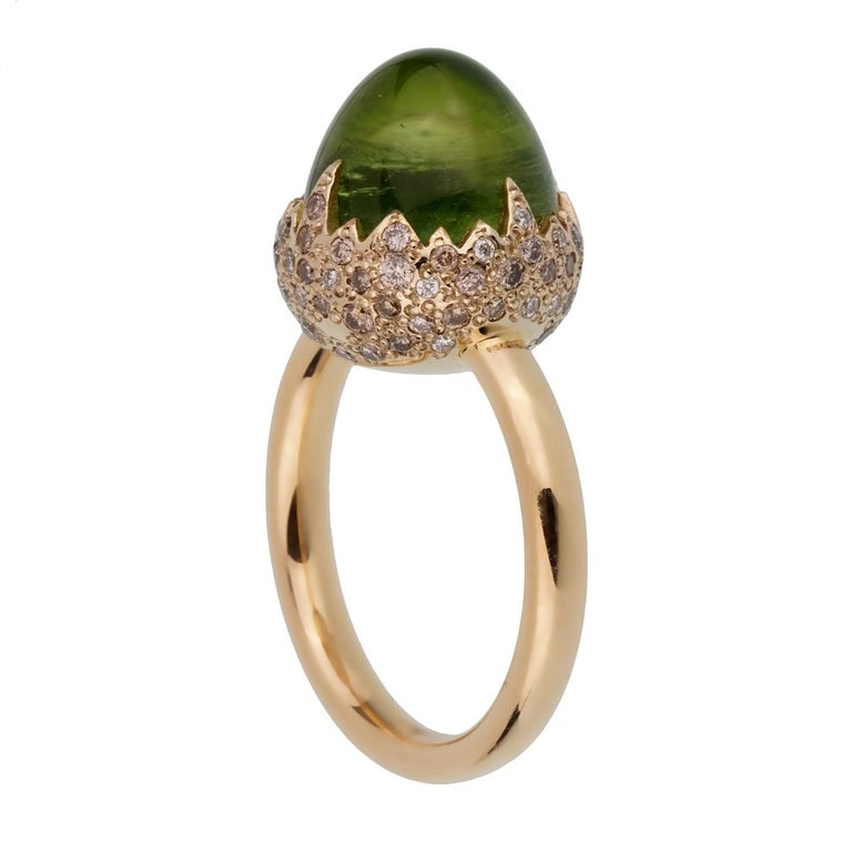 An iconic brand new Pomellato diamond cocktail ring showcasing a 8.30ct total weight Peridot encased with .25ct of round brilliant cut diamonds in shimmering 18k rose gold. The ring measures a size 6 1/2 and can be resized  Pomellato Retail Price: