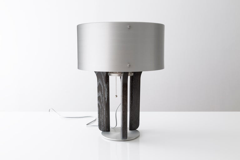 The Pommer table lamp features a satin anodized drum shade with a trumpet like interior. Warm white light radiates light from its core. LED bulbs are supplied and incandescent can be used as well. The legs of the lamp are carved from solid wood and