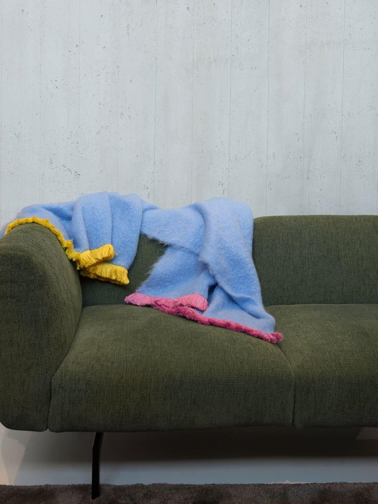Pompallier, a sweet blue throw blanket made of the finest New Zealand mohair. Characterized with a pink and yellow fringe border completely embroidered by hand. Nothing as personal as your own interior, the colors can be customized on