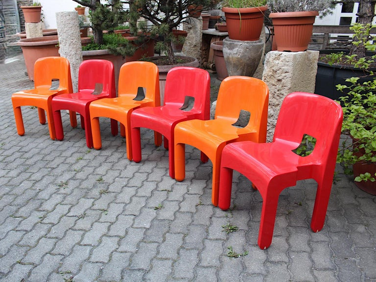 Red and orange set of six plastic space age pop art vintage chairs or dining chairs model Universale designed by Joe Colombo  1965 - 1967 and executed by Kartell, Milano. Happy making colors like cherry red and bold orange highlights this set of six
