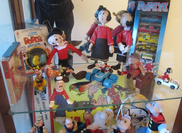 Popeye collection, 50 items, including: • 20cm high mechanical wind-up celluloid figure with pipe, • Original unopened can of 'The Allen's Popeye spinach, • Popeye 1960s Paddlewagon metal limousine, largest one made with Popeye telescope and