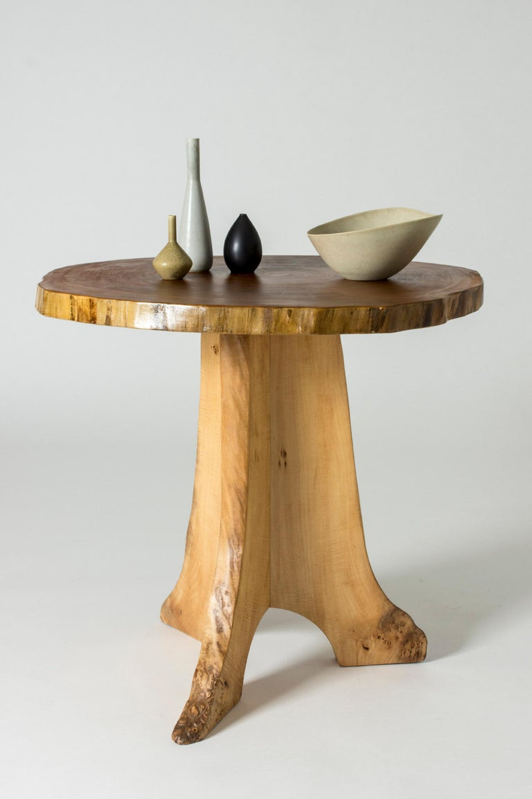 Organic occasional table by Sigvard Nilsson, made from poplar with a piedestal base. The table top is made of a sheet of a tree trunk that shows the annual rings. The base is made from pieces of wood where curves of the tree has been used to create