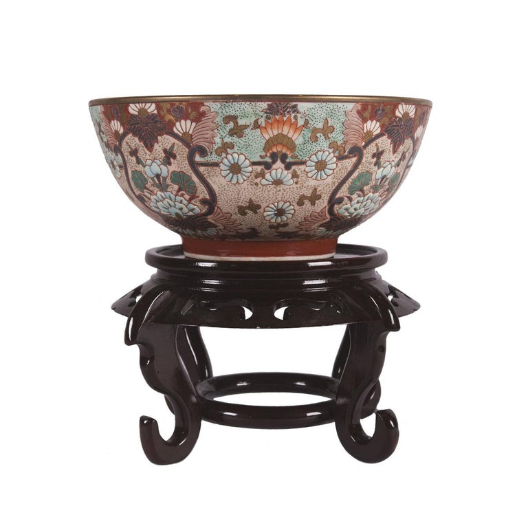 This Imari style bowl from China is hand painted and made of porcelain. This bowl includes the wooden stand shown in the photos. The bowl measures 10 inches in height and is 10 inches in diameter. The bowl is 10 inches in depth.