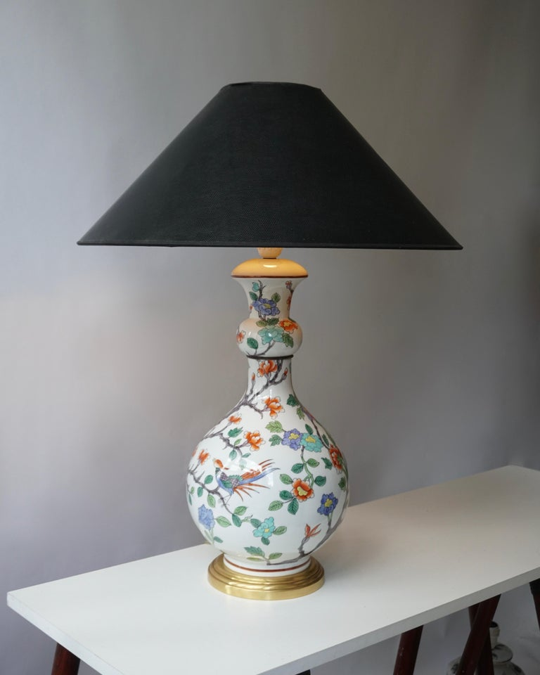 Table lamp in porcelain decorated with colorful flowers and a bird. Underside with under-glaze blue stamp 'Porcelaine de Paris, France, fondee en 1773'.  Shades shown are for demonstration purposes only. Height with shade 73 cm. Diameter 50 cm.