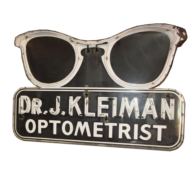 This wonderful sign once graced the entrance of an optometrists' office here in California. The face of the sign is baked porcelain enamel, and is highlighted with two colors of neon. The sign is totally self contained, and works very well. It can