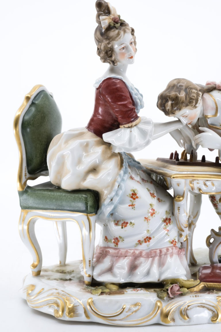 A 19th century porcelain figurine of a couple paying chess, the gentleman kissing the lady's hand.   Marked in under-glaze blue of a letter F (Fürstenberg) with a crown.    Shipping included  Free and fast delivery door to door by