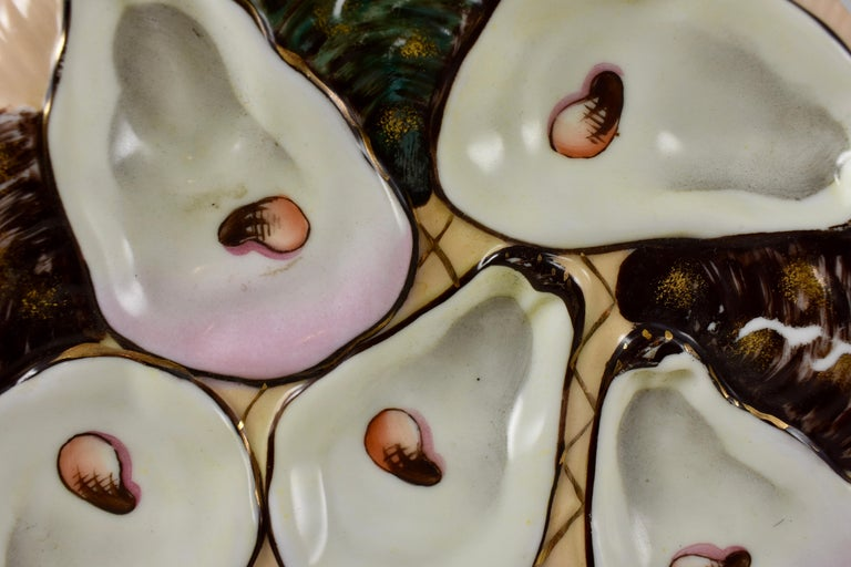 A late 19th century, French porcelain, crescent or half-moon shaped oyster plate, five pink blush oyster wells with hand-painted eyes on a salmon colored ground with a gilded fish net. Shown behind the main wells are the brown and gray glazed backs