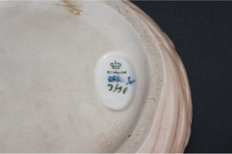A vintage porcelain bowl featuring a gray lobster on the edge of the bowl. The white porcelain is thick and its surface is colored with the typical for Royal Copenhagen,