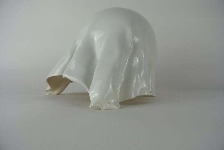 Decorative asymmetrically pleated object with white glossy glaze. White porcelain, glazed only on the outside.