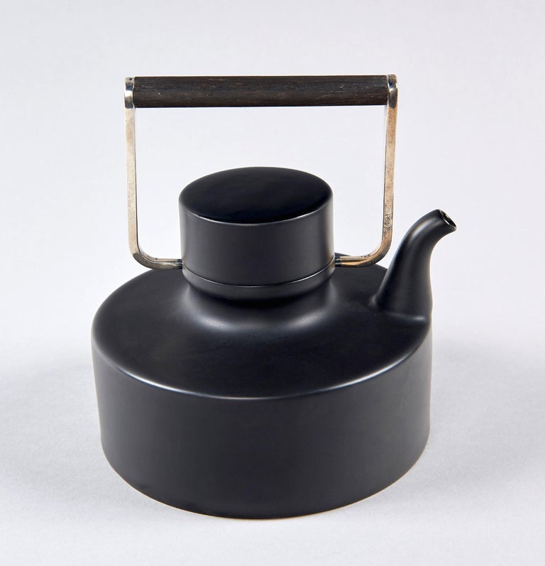 Produced in Germany by Rosenthal from 1963 until 1975 in matte black porcelain (with high gloss to the top of the lid), with a handle of teak and silver-plated brass, this exquisite teapot is unmistakably the product of multidisciplinary Finnish