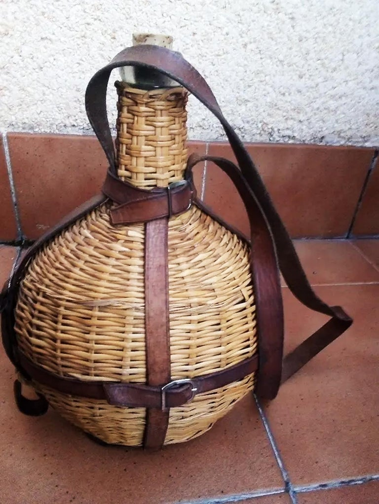 Uncommon portable wine bottle cooler. Glass, wicker and leather, Spain early 20th century, 1930 or early.  By having the glass interior, it can be used, very good conditions   Canteen or portable carafe to carry wine grated with glass or