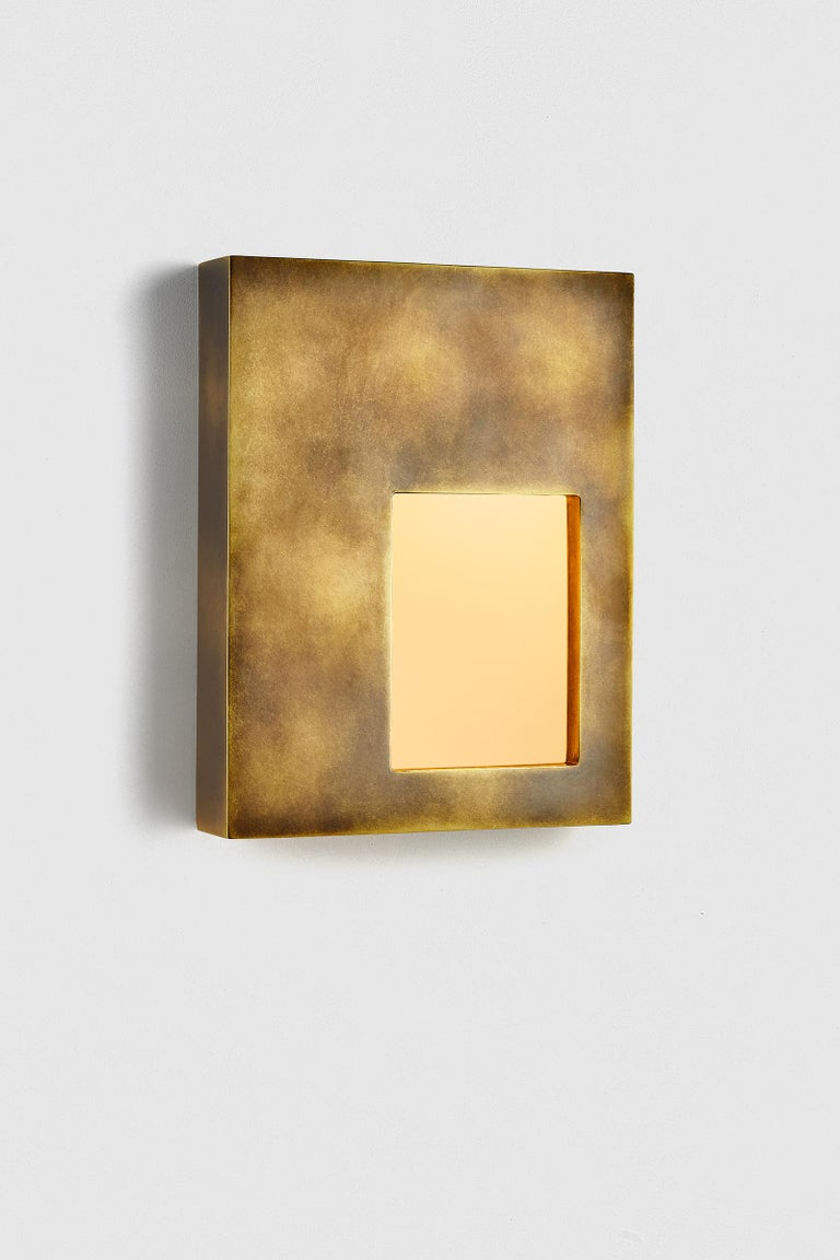 The Portal Sconce features a hand-finished brass body and an inset light diffused through textured glass, creating a warm, delicate glow.  This sconce is made from brass and is available in a polished finish or hand-applied antique finish. Please