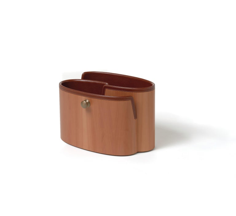 A curved profiles intertwine, echoing natural forms, in this versatile magazine container with delicate lines. The available finishings present different combinations of wood, smooth and tumbled leather, bringing out the best in each of these
