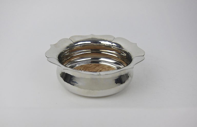 A large vintage wine or champagne bottle coaster in hand-hammered pewter by the renowned American silversmith and metal worker, Porter George Blanchard (1886-1973). This elegant hollowware vessel was designed in a floriform Arts & Crafts style with