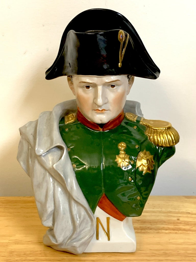 Portrait Bust of Napoleon Bonaparte, by Sitzendorf, A well executed, detailed example depicting the Emperor , dressed with bicorne hat, hunter green uniform with medals, draped with a coat, on a pedestal base with gilt 'N'. With Blue underglaze