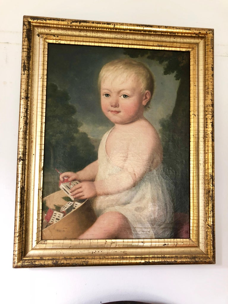 A charming oil-on-canves portrait of a young child seated with a wood band-box filled with his toys, American, early 19th century, in its original giltwood frame.