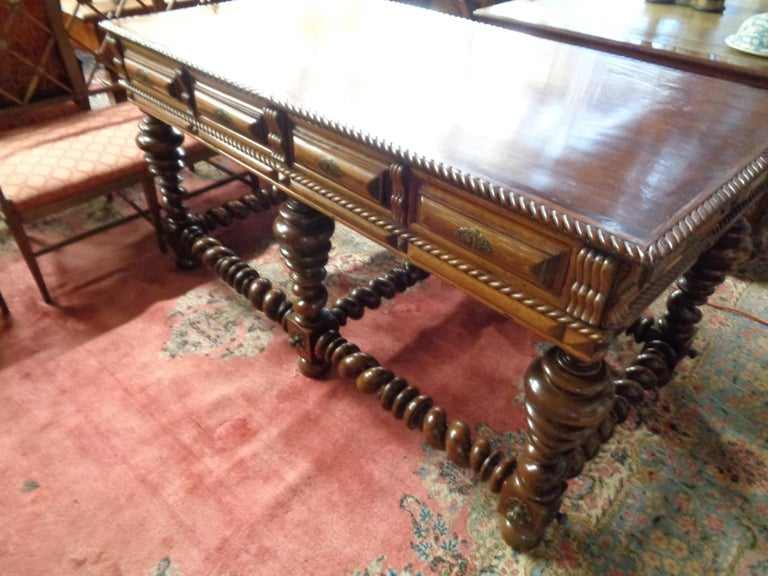 Very fine Portuguese rosewood double sided center/console table with stylized carving throughout. It has drawers on both sides and is supported by graduated bulbous turned legs. There are barley twist supports between the legs. The perimeter of the