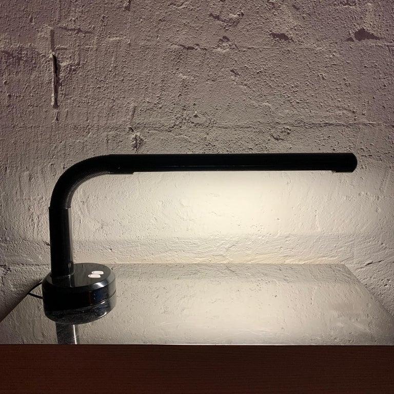 Postmodern adjustable goose neck desk or task lamp rendered in black plastic and metal.
