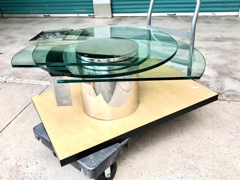 "Iconic postmodern design by Dakota Jackson. The steel base features three levels of thick glass. Referencing the self-winding clock, the two ""hands"" of the table shift under and around the round top like the hands of the clock that hover ever so"
