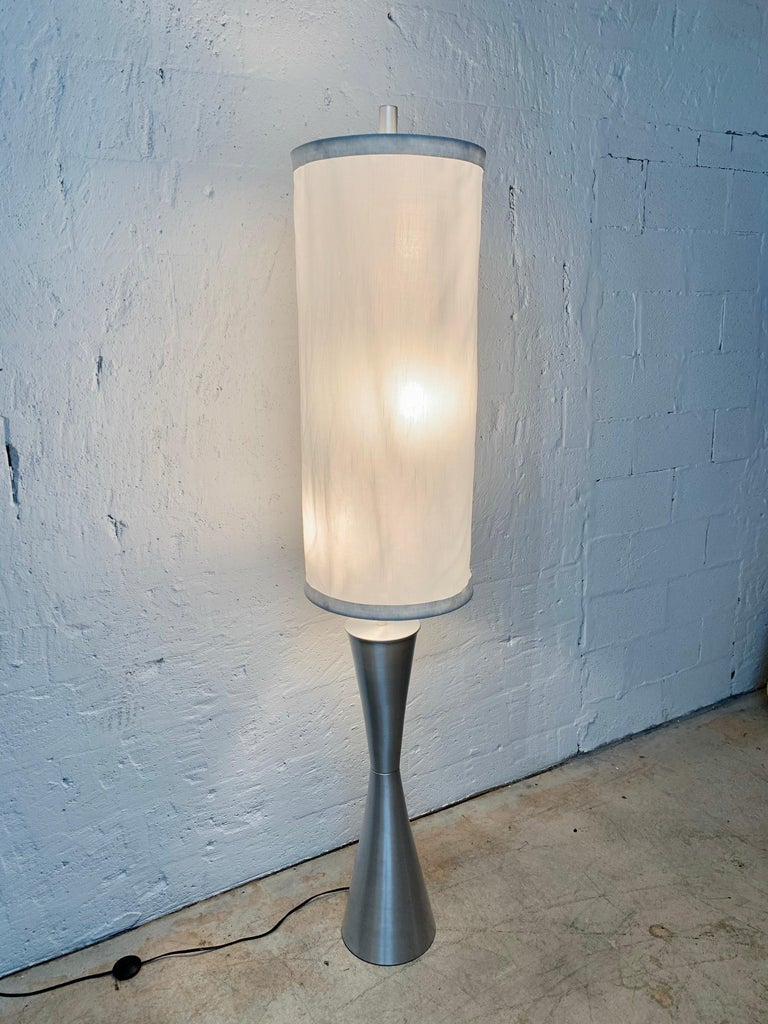 Postmodern geometric sculptural floor lamp rendered in spun aluminum base comprised of two intersecting cones with a suspended fabric shade, USA, 1980s.