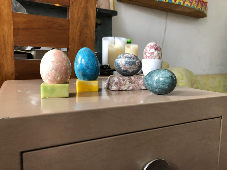Carefully curated set of semi-precious stone eggs in vibrant pastels with corresponding stone platform bases for display. Set is comprised of 5 eggs and 3 stone bases and one white egg holster.