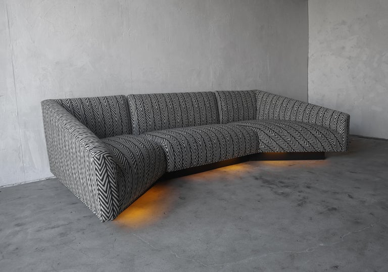 Incredible 3 piece sofa by Steve Chase. Sofa features the rarely seen, illuminated plinth base. The shape and lines of this sofa are truly eye catching. It has been modernized with a gorgeous repeating stripe zap fabric in black and cream. During