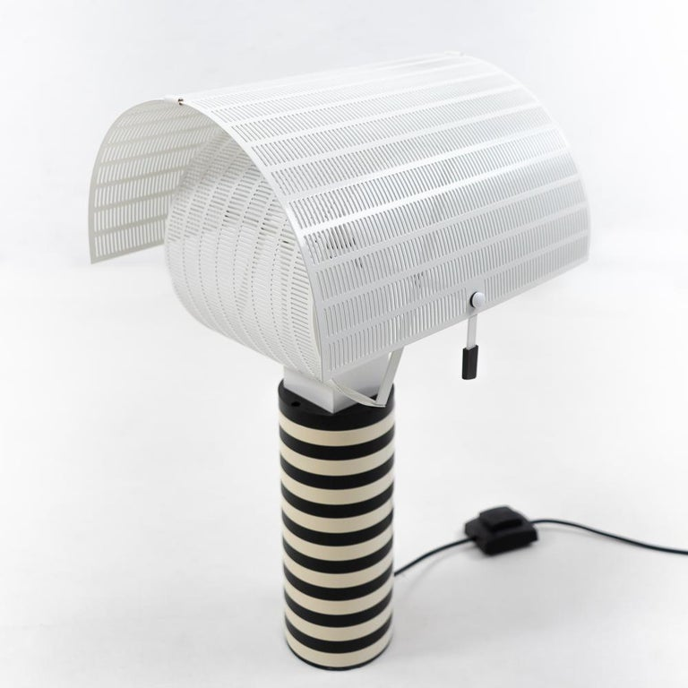 Vintage Artemide table lamp, model Shogun – a design by the architect Mario Botta (1985).  An impressive lamp being a typical design originating from the Memphis-Milano movement.  Materials: Powder coated cast-iron base. The metal cylindrical