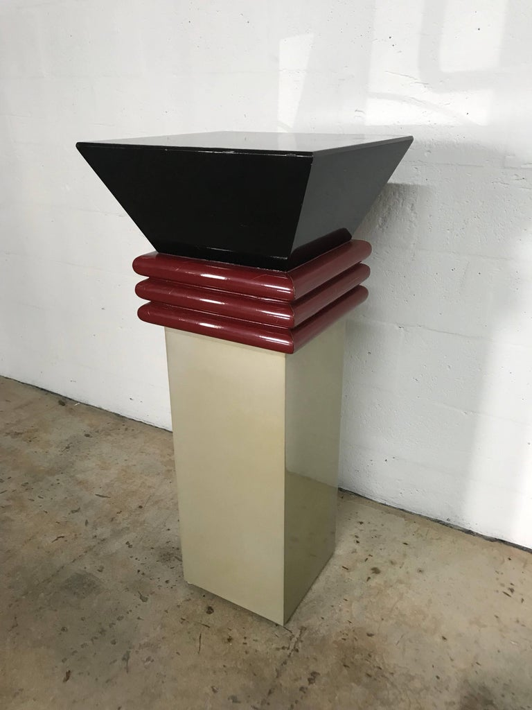 Memphis style lacquered pedestal in 3 colors, black, burgandy, and a metallic gold.  This pedestal is great for displaying objet d'art and is an art piece in it self.