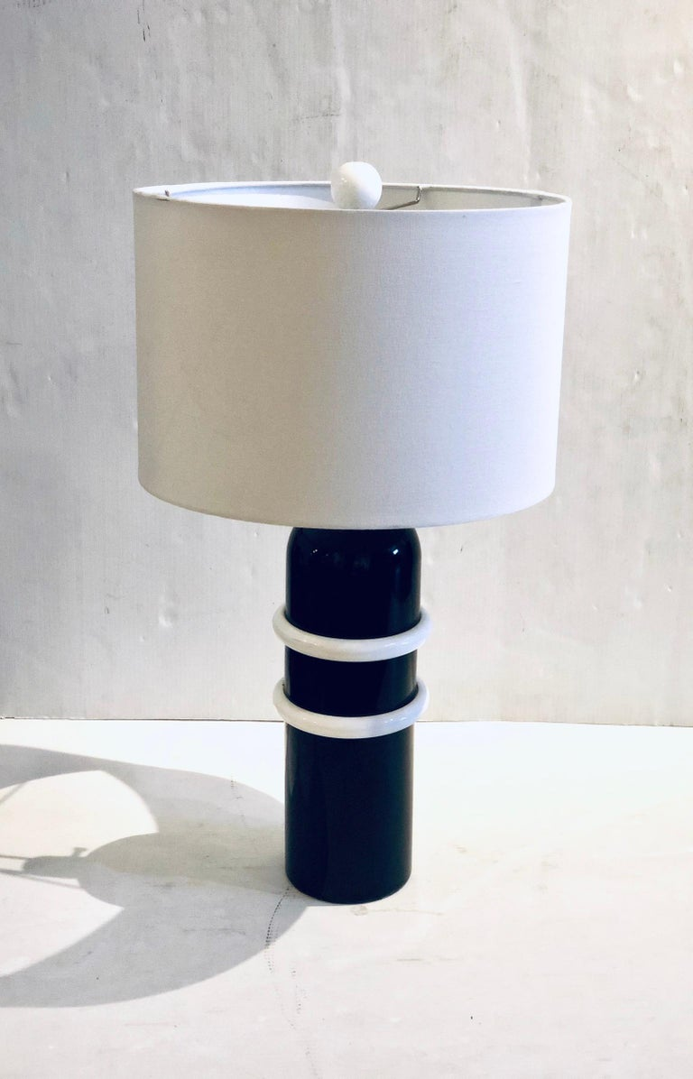 Beautiful elegant table lamp in black and white enameled finish accents, circa 1980s perfectly working with a cool white painted wood ball finial, lampshade is not included. The lamp its 28