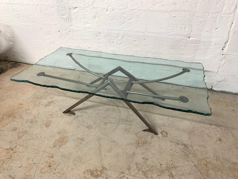 Postmodern coffee or cocktail table with a Steampunk mechanical quality, comprised of steel armature base and a sandblasted chiseled edge glass top, 1980s.