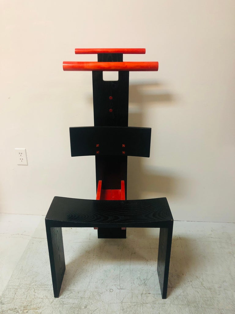 A post modern chair or valet. Spectacular design that elevates a practical piece of furniture to the realm of art. Colorful accents that accentuate the purpose, like the 2 open compartments on the horizontal planes, and the 2 notched dowels on the