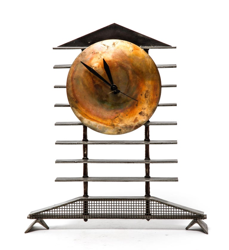 Post-modernist mantel clock made of steel and brass. The piece has a quartz battery movement in the back and is in great vintage condition, with some minor age-related wear to the metal surfaces.