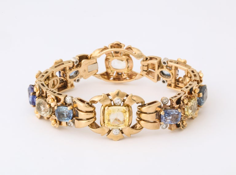 Pastel blue and yellow cushion cut sapphires are alternately set and highlighted with diamonds in this elegant vintage Cartier bracelet.  Made by
