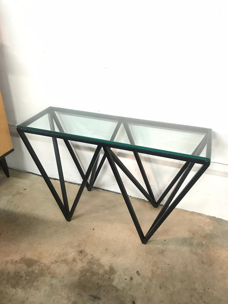 Structural Postmodern console table rendered in black painted steel and glass.