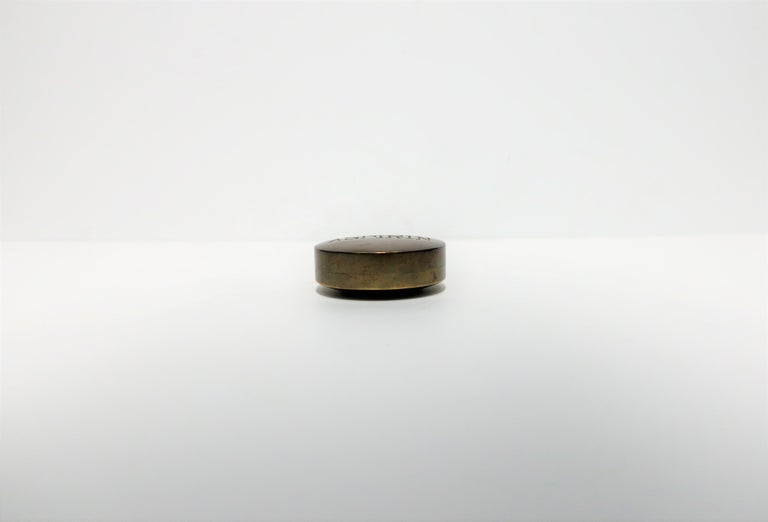 A substantial round Postmodern 'ASPIRIN' brass 'pill' box, late-20th century, circa 1970s. Box is an oversized 'aspirin' in solid hand-cast brass and embossed on top in all caps is the word 'ASPIRIN'. A great piece representative of the Postmodern