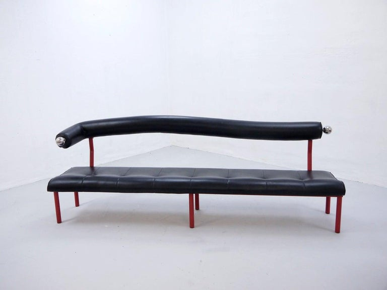 Large vintage sofa bench with black faux leather (vinyl) seating, curved backrest, red-lacquered metal frame and chrome decorations  Unknown origin  Beautiful Postmodern 1980s design  The bench is in very good original condition, with few
