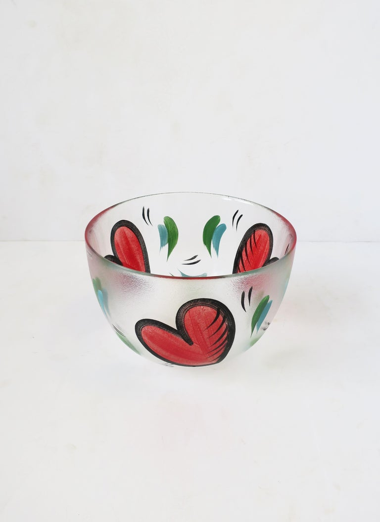 A fun and beautiful Postmodern Swedish bowl, hand painted with big red hearts, signed by Artist, Ulrica Hydman-Vallien, for Kosta Boda, Sweden, late 20th century. Artist/designer: Ulrica Hydman-Vallien (b. 1938-d. 2018.) In addition to being a great