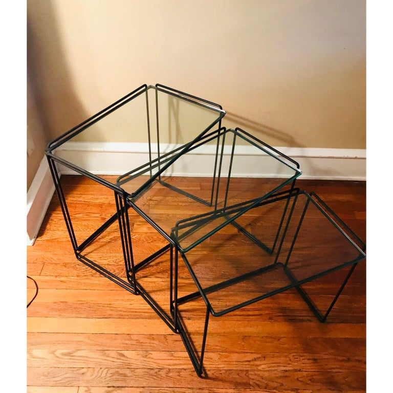 Set of Minimalist nesting tables designed by French designer Max Sauze.   Manufactured for Attrow, circa 1960s.   Simple design with welded black wrought iron and glass.   I would say this is an early example of Post-modernism, despite being