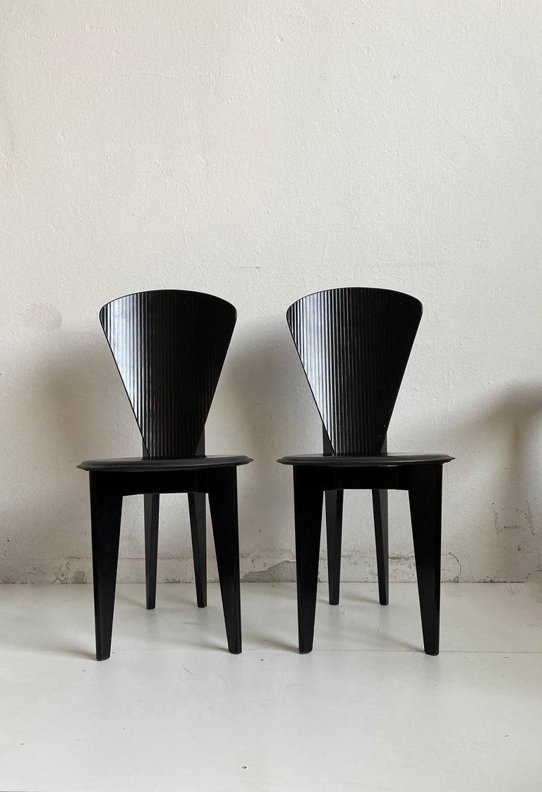 This set of two black wooden dining chairs by Calligaris was made in Italy, circa 1980.  Stunning sculptural postmodern design. These dining chairs feature a curved back with ridges and round leather seats.  There are no structural issues. The